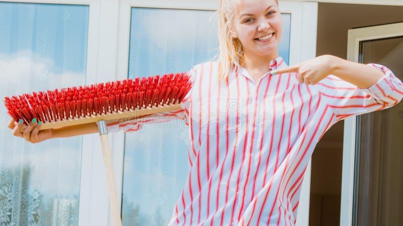 Frau, die Besen verwendet, um Hinterhofpatio aufzuräumen stockfoto