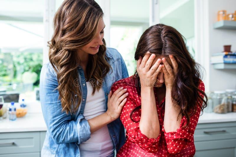 Frau, die besorgten Freund tröstet stockfoto