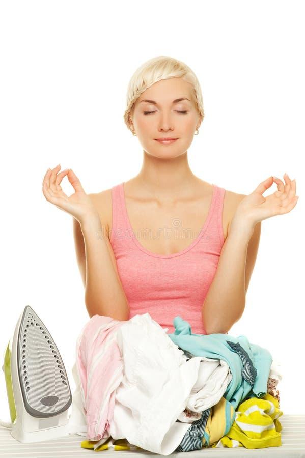 Frau, die bevor dem Bügeln meditiert stockbild
