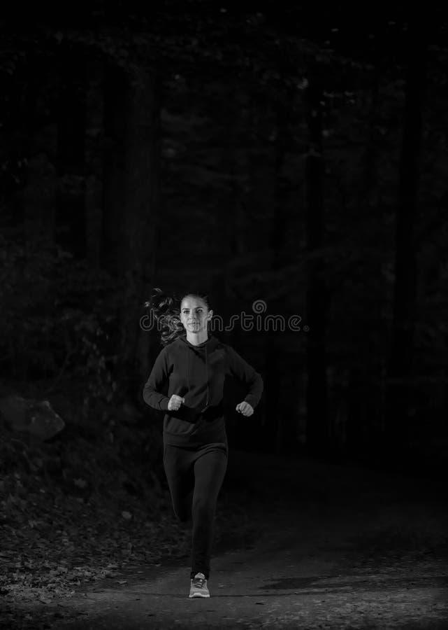 Frau, die in bewaldeten Waldbereich, Training läuft und für Hinterläufermarathonausdauer trainiert lizenzfreie stockfotografie