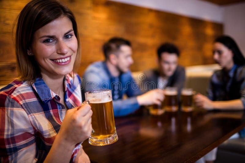 Frau, die Bierkrug während Freunde im Hintergrund hält stockfoto