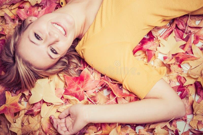 Frau, die in Blätter legt stockfotos