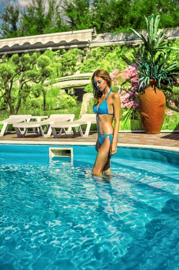 Frau, die blauen Bikiniaufenthalt Wasserpool im im Freien auf Erholungsort trägt lizenzfreie stockfotos