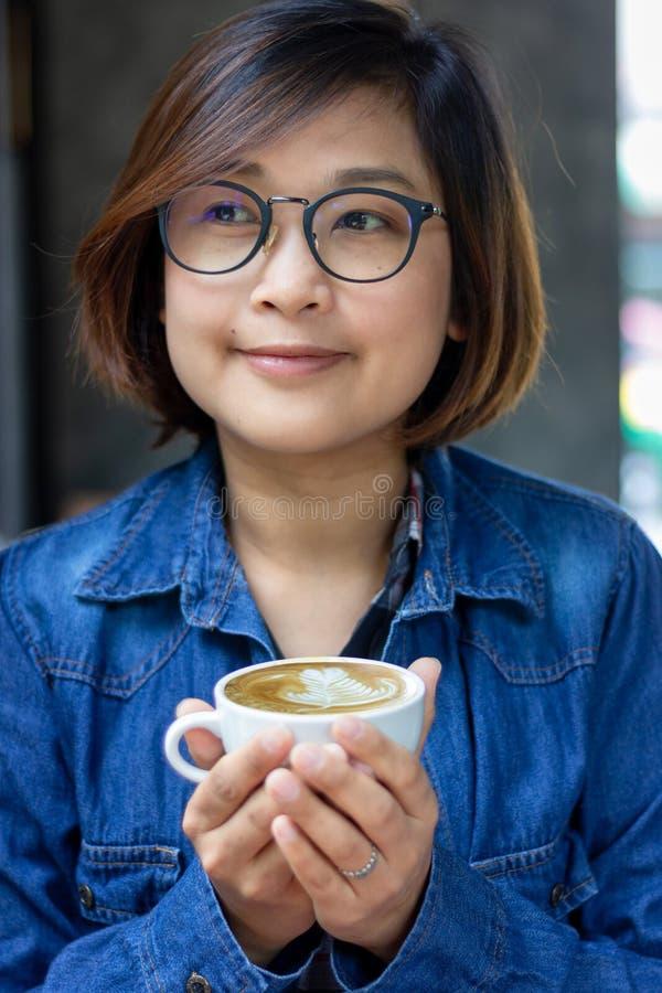 Frau, die blaues Baumwollstoffhemd und -hand h?lt eine Schale flachen wei?en Kaffee tr?gt lizenzfreies stockbild