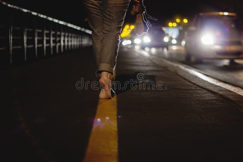 Frau, die bloßen Fuß auf Spitzenzehen in der Nacht mit kommendem Verkehr geht stockbilder