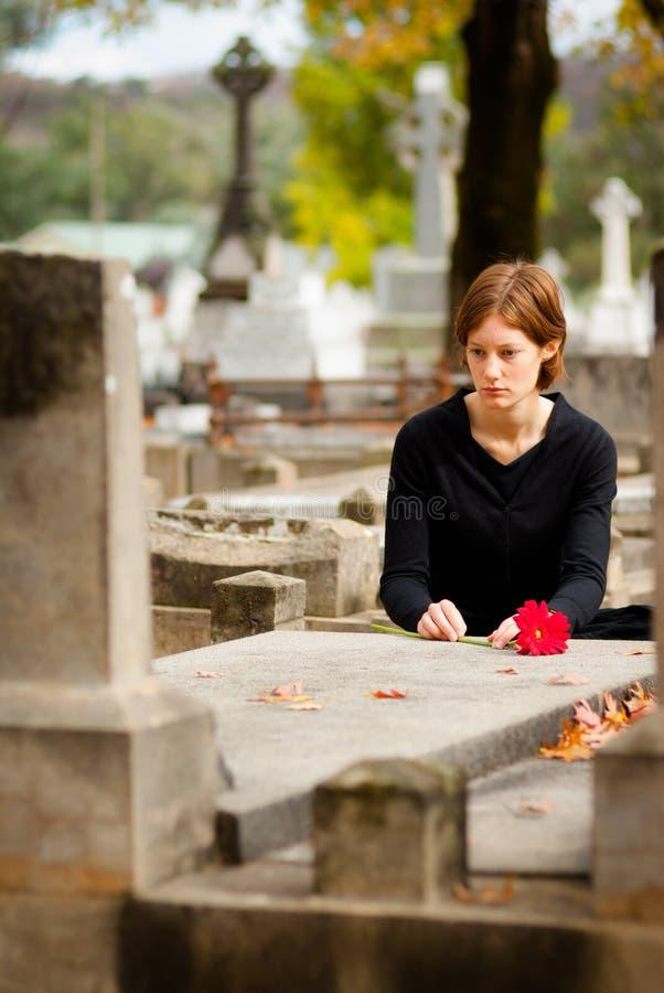 Frau, die Blume auf Grab legt stockfotos