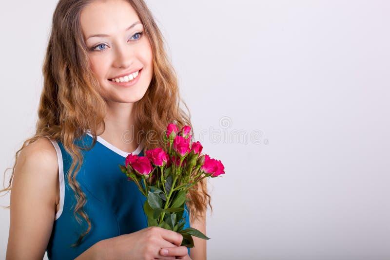 Frau, die Blumenstrauß der Rosen anhält lizenzfreie stockbilder
