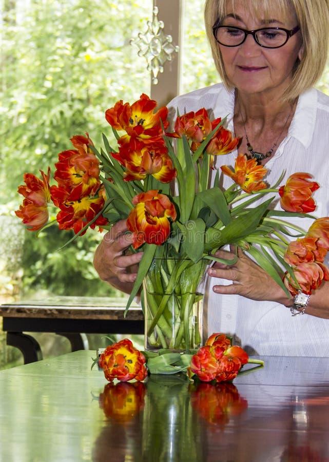 Frau, die Blumenstrauß von bunten Tulpen vereinbart stockfoto