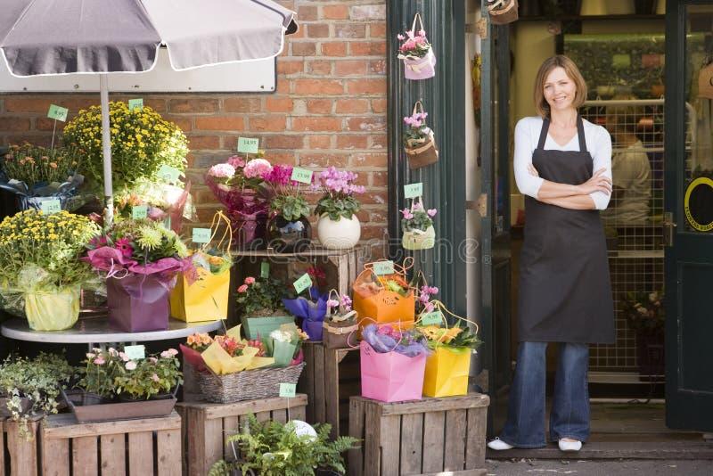 Frau, die am Blumensystemlächeln arbeitet lizenzfreies stockbild