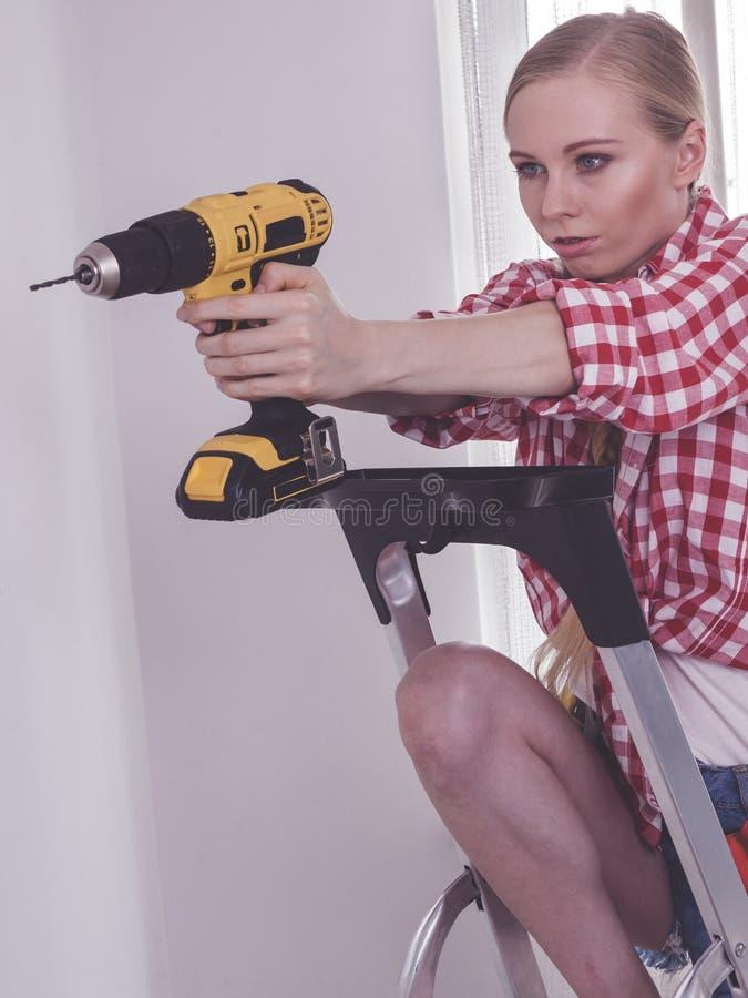Frau, die Bohrger?t auf Leiter verwendet stockbild
