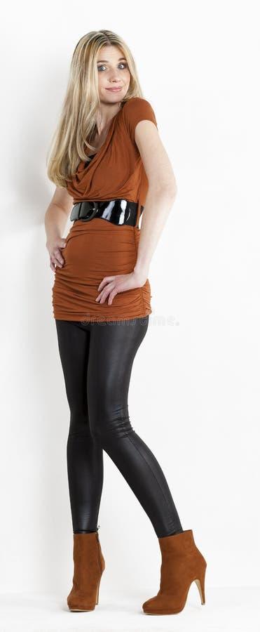 Stehende Frau, die trägt Mantel und modische Braune Schuhe