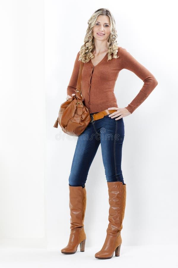 Frau, die braune Stiefel mit einer Handtasche trägt lizenzfreies stockfoto