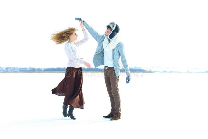 Frau, die braunes Rock- und Strickjackentanzen mit Mann im Schneehintergrund trägt stockfotografie