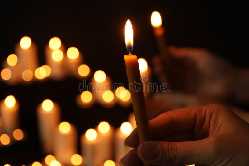 Frau, die brennende Kerze in der Dunkelheit gegen unscharfen Hintergrund, Nahaufnahme hält stockfoto