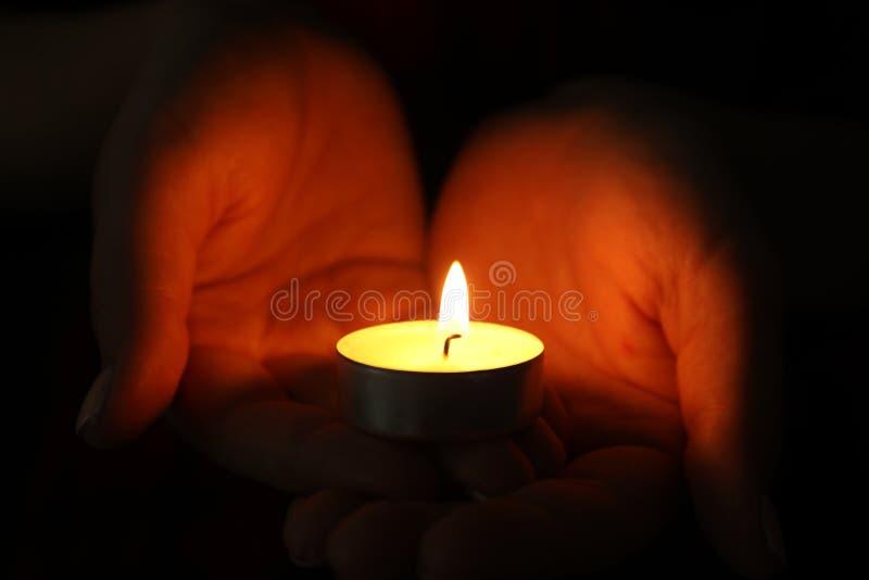 Frau, die brennende Kerze in der Dunkelheit hält stockfoto