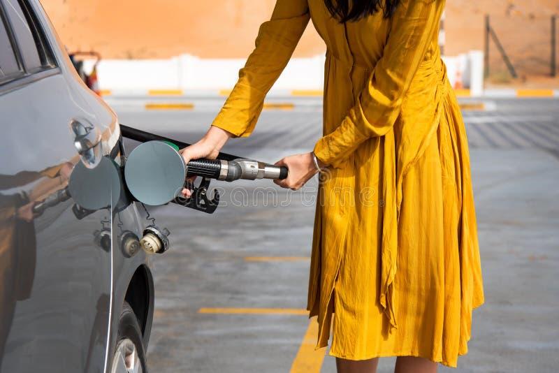 Frau, die Brennstoff auf der Tankstelle hinzufügt lizenzfreies stockbild