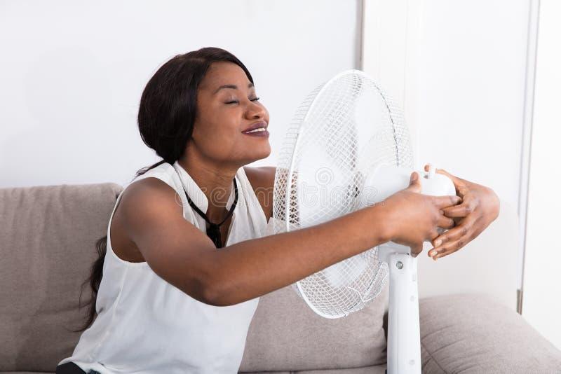 Frau, die Brise mit elektrischem Ventilator genießt lizenzfreie stockfotos