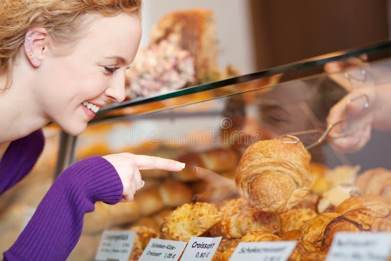 Frau, die Brot vom Verkaufsmöbel vorwählt stockfotos