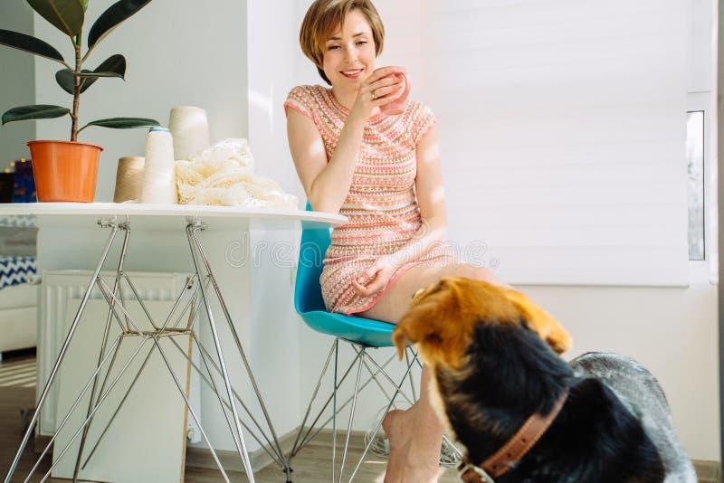 Frau, die Bruch mit Kaffeetasse beim Spitzetischdecke mit Häkelarbeit zu Hause stricken an dem gemütlichen Arbeitsplatz Innen hat stockfoto