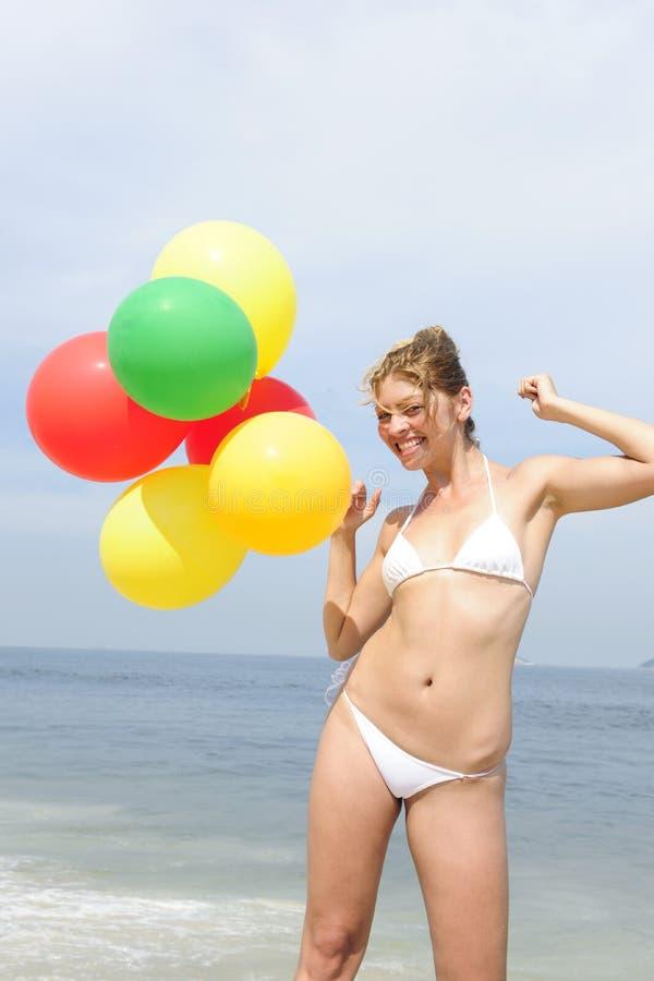 Frau, die bunte Ballone auf dem Strand anhält stockfotografie