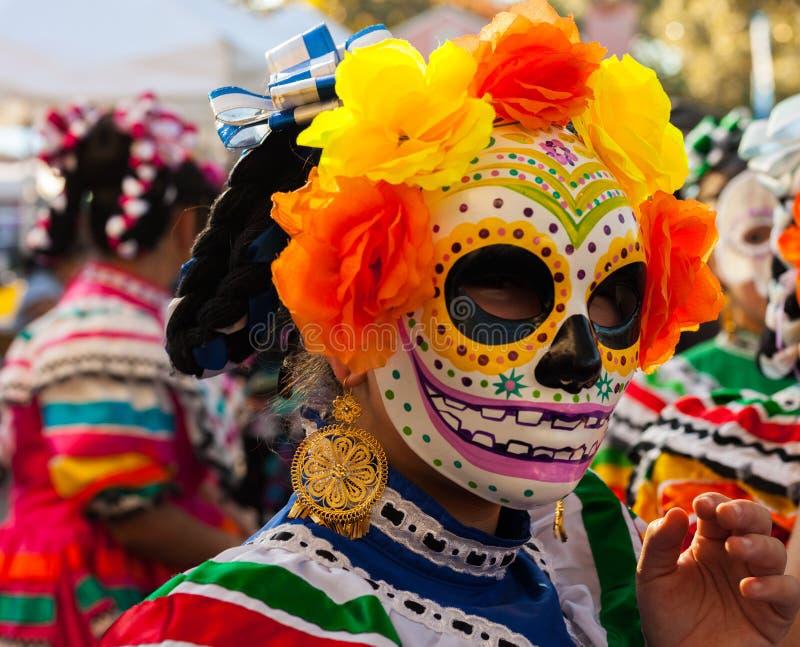 Frau, die bunte Schädelmaske und Papierblumen für Dia de Los Muertos /Day der Toten trägt stockfoto