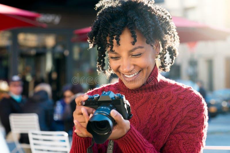 Frau, die in camera Bilder betrachtet stockbilder