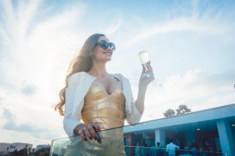 Frau, die Champagner am Sommerfest isst lizenzfreies stockbild