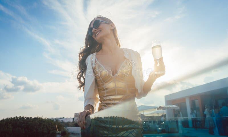 Frau, die Champagner am Sommerfest isst stockfotografie