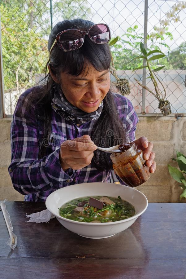 Frau, die Chili Oil In Laos Noodle-Suppe setzt stockfotografie