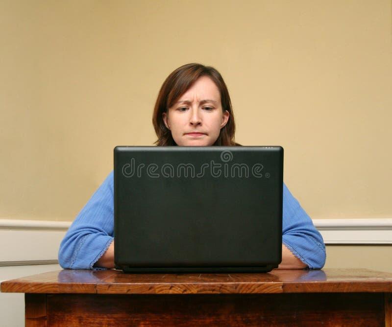 Frau, die am Computer die Stirn runzelt lizenzfreie stockfotografie