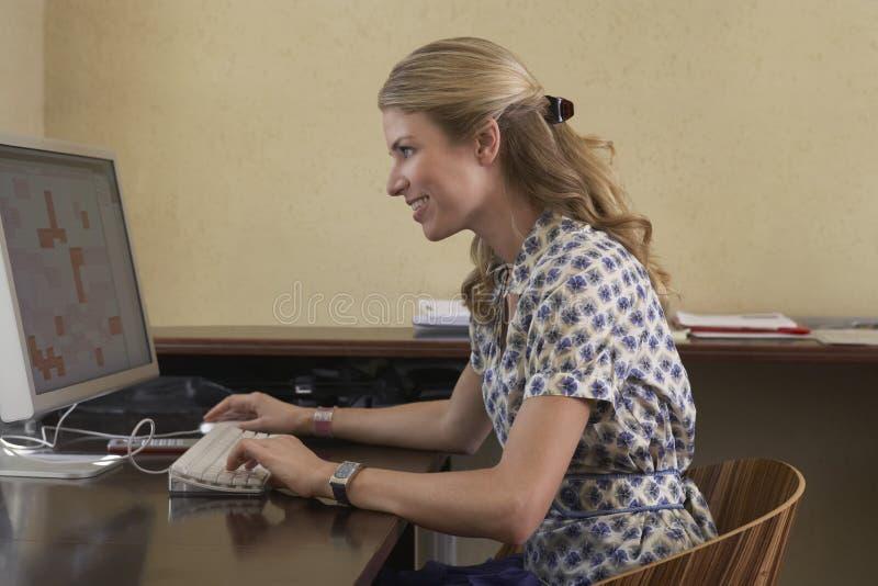 Frau, die Computer im Büro verwendet stockbild