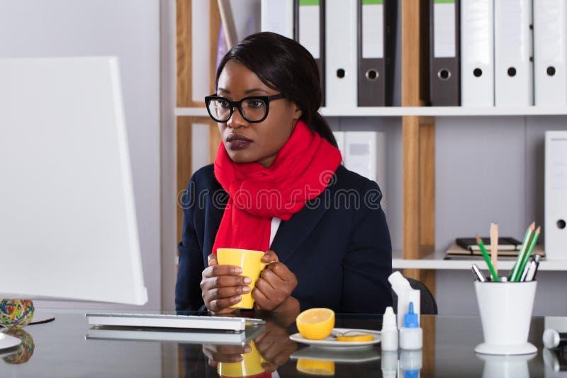 Frau, die an Computer mit Tasse Tee arbeitet stockbilder