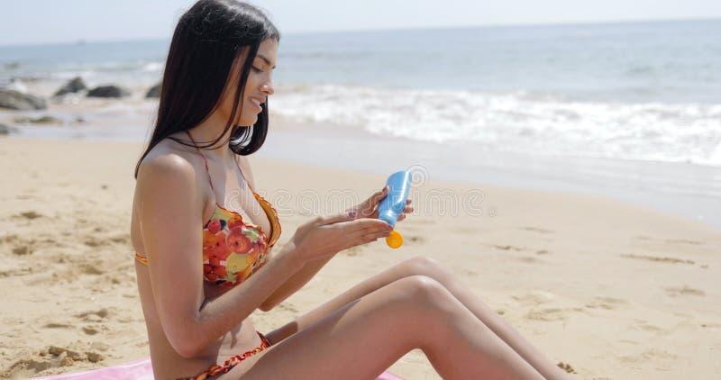 Frau, die Creme auf Strand aufträgt stockfoto