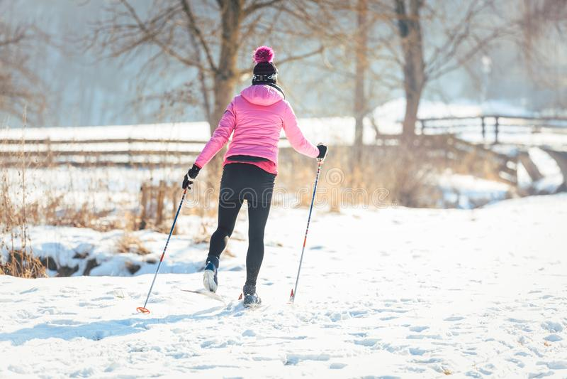 Frau, die Cross Country-Skifahren als Wintersport tut stockfotografie