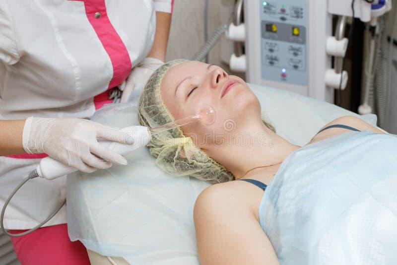 Frau, die darsonval im Gesichttherapie an der Cosmetologyklinik erhält lizenzfreie stockfotos