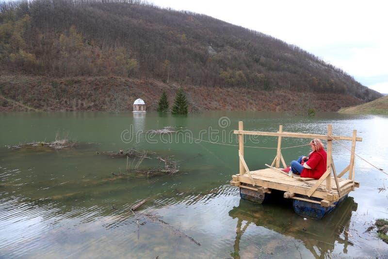 Frau, die das Überschwemmung Kloster Valjevska Gracanica im See schaut stockfotografie