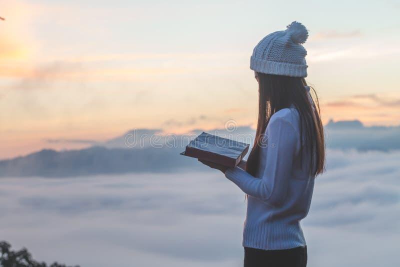 Frau, die das Ablesen der Bibel auf Berg im Morgen-Bild hält stockfoto