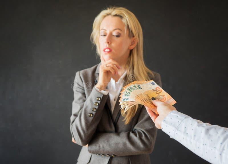 Frau, die an das Annehmen des Bestechungsgelds denkt stockbild