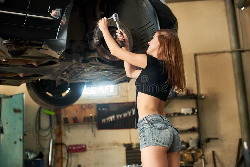 Frau, die das Auto mit Sockelschlüssel auf Hebebühne repariert lizenzfreie stockbilder