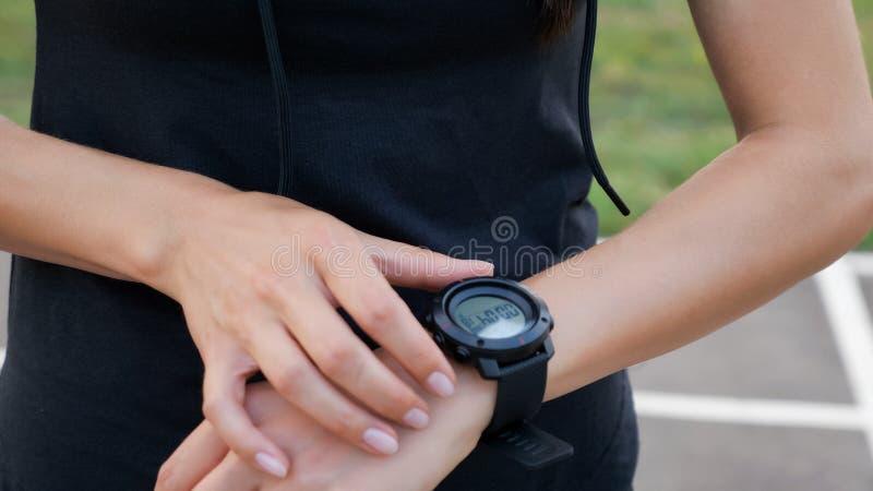 Frau, die das Eignung smartwatch für das Laufen gründet Sportliches Mädchen, das oben Uhrgerät, Abschluss überprüft stockfotos