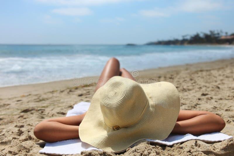 Frau, die das Ein Sonnenbad nehmen am Strand ausbreitet lizenzfreies stockfoto