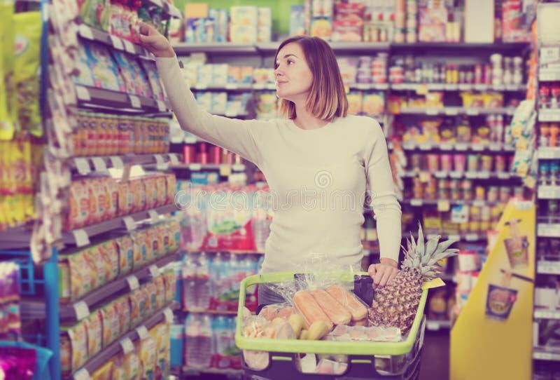 Frau, die das Einkaufen mit Warenkorb tut lizenzfreies stockbild