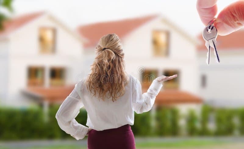Frau, die das Haus zu verkaufen zeigt lizenzfreie stockfotos