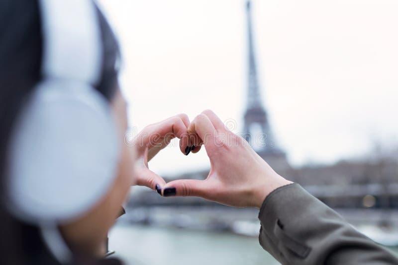 Frau, die das Herzsymbol mit seinen Händen zum Eiffelturm vom Fluss die Seine in Paris, Frankreich macht stockfotografie
