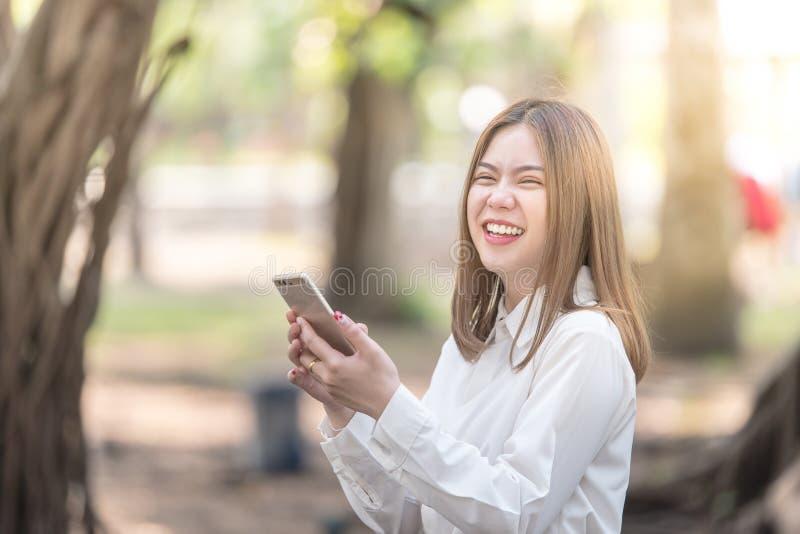 Frau, die das intelligentes Telefonlachen und -lächeln verwendet lizenzfreies stockbild