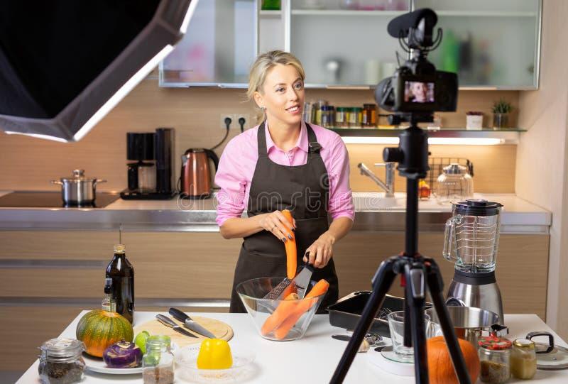 Frau, die das Kochen des vlog, notierend auf Kamera macht lizenzfreies stockfoto