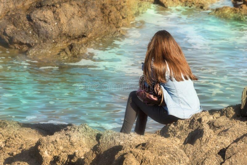 Frau, die das Meer sitzt allein, hintere Ansicht schaut lizenzfreie stockbilder