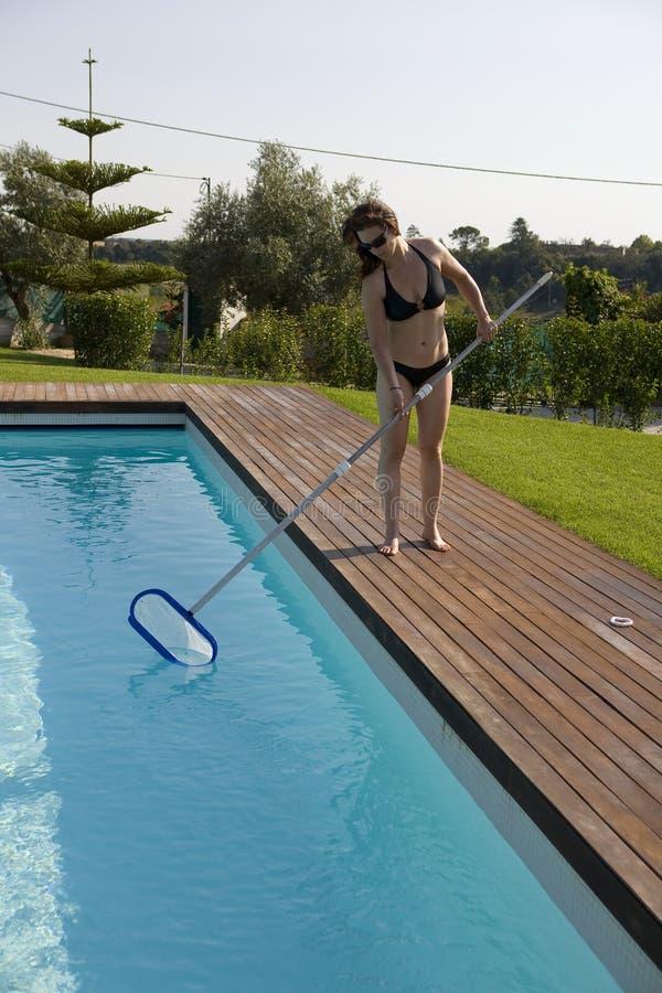 Frau, die das Pool säubert lizenzfreie stockbilder