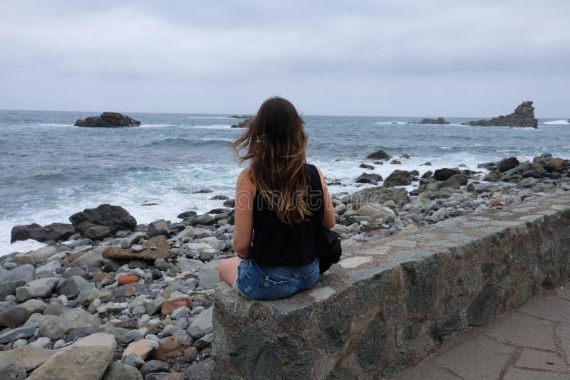 Frau, die das raue Meer auf felsigem Strand betrachtet lizenzfreie stockfotos