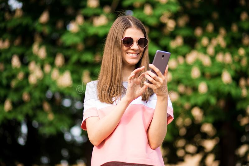 Frau, die das rosa Hemd simst am intelligenten Telefon geht in die Straße trägt lizenzfreies stockfoto